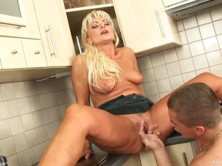 Blonde haired milf Sadie has sex with curious guy in the kitchen. She spreads her legs and gets her snatch licked and fingered by hot guy. She begs for twat fucking after oral-job fun.