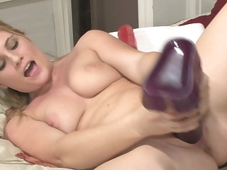 A blonde is pushing large toys deep inside her wet and succulent cunt