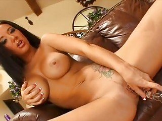 Tanned dark haired pornstar with tattoo and pierced cunt uses glass dildo